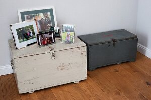 Two wooden trunks with collection of family photos on top of one