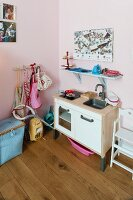 Toy kitchen and blue-painted bracket shelf on pink-painted wall in corner of child's bedroom