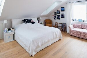 Double bed with headboard and white bedspread and patterned sofa in attic bedroom