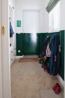 Cloakroom with lower half of walls and door painted glossy dark green