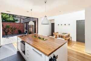 Kitchen island with wooden worksurface below retro pendant lamps; open folding doors leading to courtyard in background