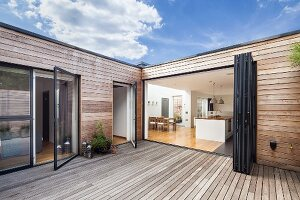 View from wooden deck of wood-clad contemporary house through open folding doors into kitchen
