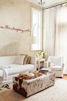 Text artwork on sand-coloured wall above sofa with white loose cover and ottoman with animal-skin cover