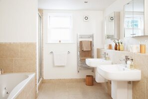 Pale bathroom with twin sinks on projecting wall below mirrored cabinets and sand-coloured tiles on floor and walls