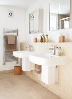 Twin sinks on projecting wall with sand-coloured tiles below mirrored cabinets on wall and brown towels on stainless steel towel rack in corner