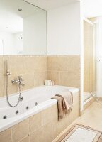 Fitted bathtub against half-height, sand-coloured tiles below large mirror on wall and separate shower cubicle with glass door in background