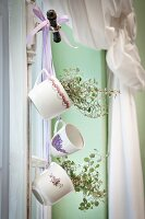 Cups hung from window handle by coloured ribbons, some planted with Muehlenbeckia