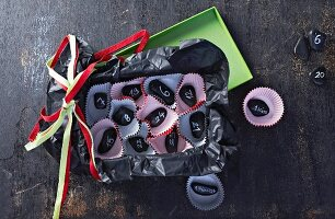 Hand-crafted Advent calender made from small paper cake cases and black pebbles
