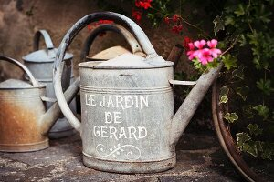 Old watering cans on stone flags in front of house