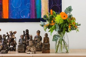 Collection of carved wooden figurines next to summery bouquet on sideboard below partially visible artwork on white wall