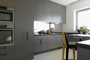 Minimalist kitchen with grey doors; wooden bar stool in foreground