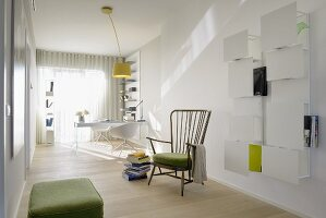 Minimalist, light-flooded study with white, wall-mounted shelves and vintage wooden armchair