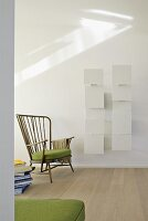 Modern shelving with white screen elements behind fifties-style armchair