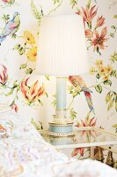 Wallpaper with pattern of flowers and parrots, table lamp with pleated lampshade on bedside table and partial view of bed