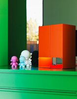 Orange, cubic table lamp and small plastic figurines on green cabinet