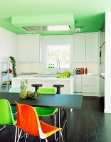 Colourful plastic chairs at black table, dark wooden floor, white modern counter and fitted kitchen in background below green-painted ceiling in open-plan interior