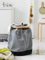 A wooden stool with a homemade, black-and-white striped fabric bag as a laundry basket in a modern bathroom