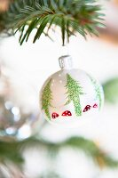 White Christmas tree bauble with pattern of spangled fir trees and fly agaric toadstools