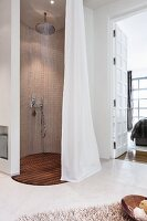 An oval rain shower cubicle with a limestone mosaic wall, a teak floor grating and a curtain in a cosy en suite bathroom with a view through a frame and panel door into the bedroom