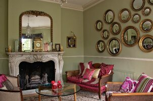 Gallery of gilt-framed, convex mirrors in interior with antique, re-upholstered seating, 60s glass table and historical fire surround