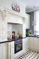Cooker and integrated cupboards in white mantel hood in country-house kitchen