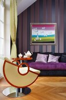 Designer armchair and side able in front of purple sofa and picture on striped wallpaper
