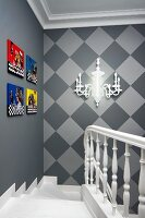 Head of staircase on elegant lantern with brightly coloured pictures and sconce lamp on walls in shades of grey