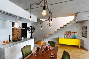 Rustic ceiling lamp made from branch above dining table next to kitchen island; yellow sideboard below exposed concrete staircase in background