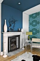 Ornaments on mantelpiece on blue wall; armchair and side table with chrome frame against accent wall with patterned wallpaper
