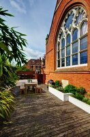 Furnished wooden deck with raised beds adjoining brick facade of Neogothic church