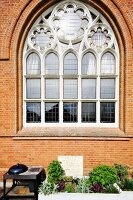 Neogothic rose window in brick façade of converted church above raised beds and barbecue on terrace