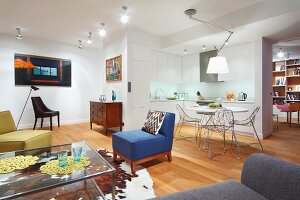 Colourful armchairs, glass coffee table, cowhide rug and wooden floor; dining area with wire chairs and open-plan kitchen in background