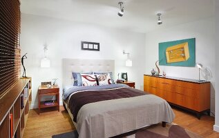 Double bed with upholstered headboard next to fifties-style sideboard in modern bedroom