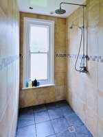 Narrow shower room with window and marble tiles