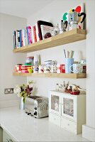 Wooden shelves of books and crockery on wall above retro toaster on kitchen counter