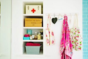 Storage boxes on shelving in niche and bags hanging from wall hooks