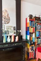 Painted plastic bottles used as flower vases on mantelpiece next to patchwork-style bookshelves