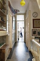Narrow landing in traditional house with head of staircase to one side and woman in kitchen at far end