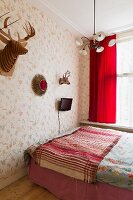 Simple double bed with striped blanket and stylised hunting trophies and TV on wall with floral wallpaper