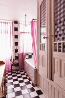 Vintage bathroom with chequered floor and wall, pink curtain on window and white-painted fitted cupboards to one side