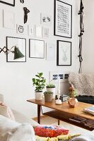 Potted plants on wooden coffee table in corner of living room and gallery of framed pictures on wall