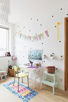 Yellow chair at white desk, heart shaped stickers and bunting on wall of child's bedroom