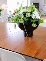 Hydrangeas and white dahlias in black designer vase on wooden table