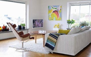 Sofa, swivel chair and retro table in Scandinavian living room; TV and modern artwork in background