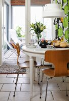 Round breakfast table with Scandinavian laminate-wood chairs and view into conservatory in background