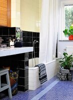Tiles in mixture of colours and formats in bathroom; bathtub with shower curtain, masonry washstand and towels