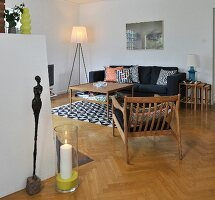 Wooden armchair, coffee table and nest of tables, rug and scatter cushions with geometric patterns, sculpture and candle lantern in living room