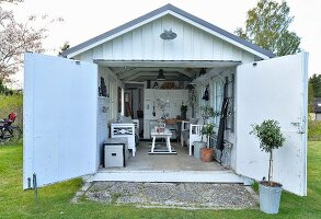 View into converted garage with cosy, vintage furnishings and storage for gardening implements