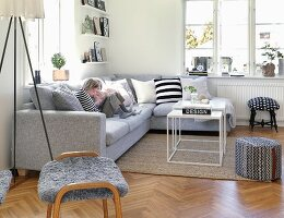 Young children sitting on grey sofa in modern living room with Scandinavian ambiance
