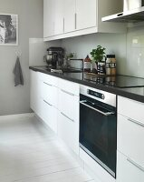White, designer kitchen with splashback and white-painted wooden floor